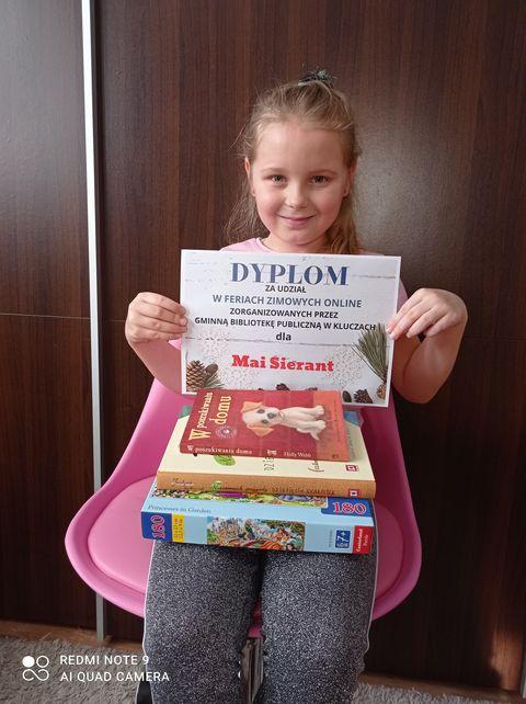 Na zdjęciu dzieczynka siedzi na krześle i pokazuje dyplom i nagrody książkowe które dostała