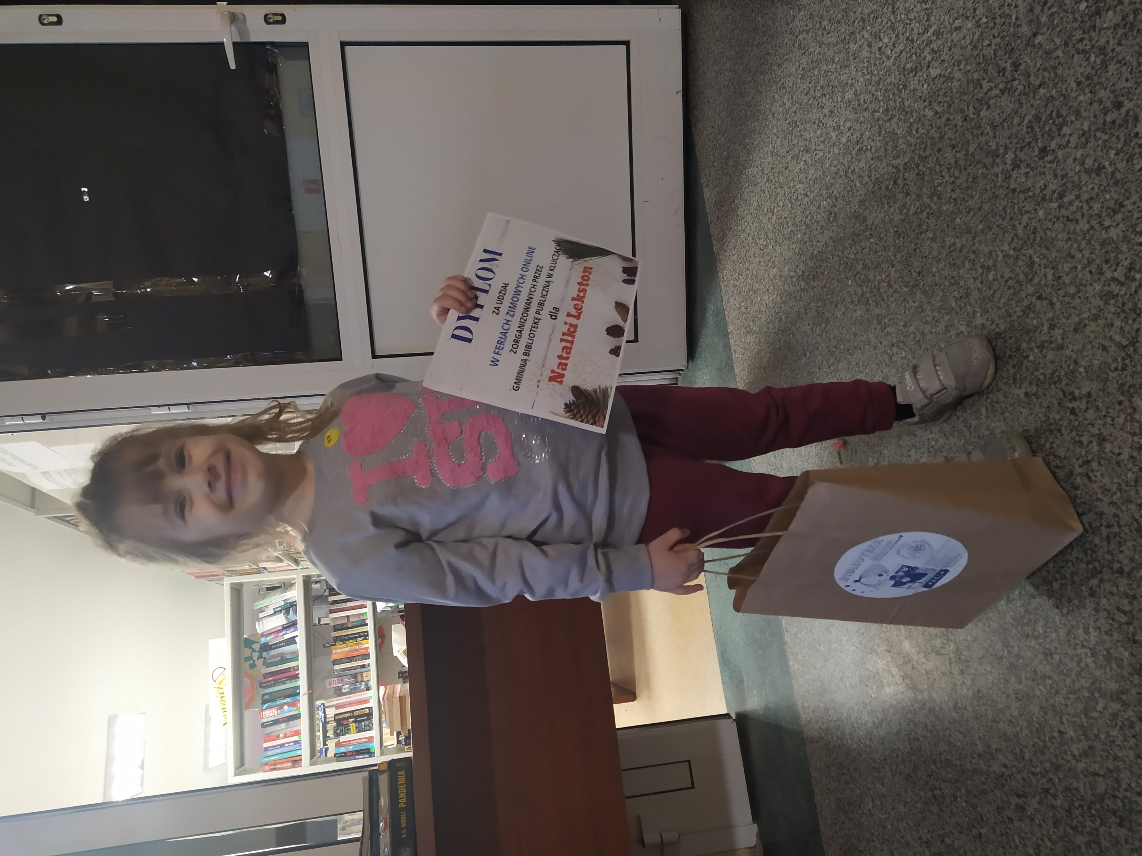 Na zdjęciu dzieczynka, która stoi prerzed wejściem do biblioteki i usmiechnięta trzyma dymlom w prawej dłoni, a w lewej torbę papierową z nagrodami. Za dziewczynką stoi stolik koloru brazowego, a za stolikiem widac regła w ksiązkami